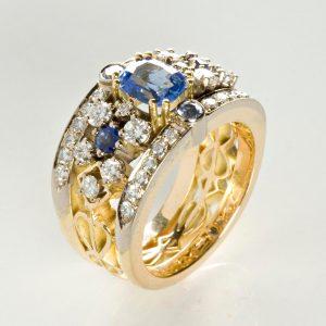 18 karaat wit- en geelgouden ring met een lichtblauwe saffier en briljant. Lichte uitvoering. De kleine kleurstenen zijn ook saffieren.