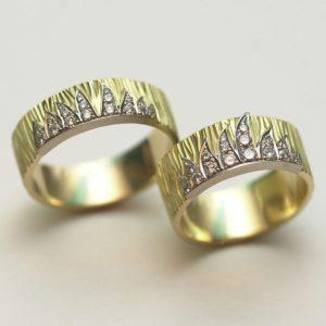 Twee 18 karaat geelgouden ringen met boomschors motief en witgouden vlammen bezet met briljanten.